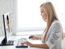 Empresaria que tiene llamada video en el ordenador fotografía de archivo