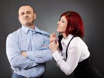 Empresaria que tira de la corbata del hombre de negocios Imagen de archivo libre de regalías