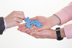Empresaria que toma pedazos del rompecabezas a disposición de hombre en oficina Fotos de archivo libres de regalías