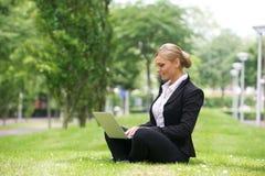 Empresaria que trabaja al aire libre en el ordenador portátil Foto de archivo