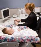 Empresaria que trabaja con el bebé en el escritorio Fotografía de archivo libre de regalías
