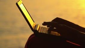 Empresaria que trabaja con el ordenador portátil en la playa Ascendente cercano de la computadora portátil La muchacha trabaja en metrajes