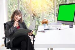 Empresaria que trabaja delante de la lectura del ordenador que piensa en monitor de la visión del proyecto imagen de archivo libre de regalías