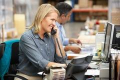 Empresaria que trabaja en el escritorio en Warehouse Fotografía de archivo libre de regalías