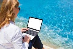 Empresaria que trabaja en el ordenador portátil de vacaciones por la piscina foto de archivo
