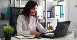 Empresaria que trabaja en el ordenador portátil y que cuenta en la calculadora en oficina moderna metrajes