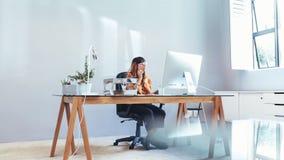 Empresaria que trabaja en el ordenador que se sienta en oficina fotos de archivo libres de regalías