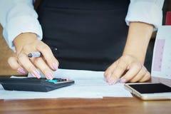 Empresaria que trabaja en la calculadora con el teléfono móvil Fotos de archivo libres de regalías