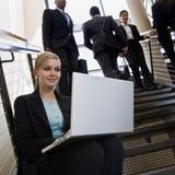 Empresaria que trabaja en la computadora portátil en las escaleras de la oficina Fotografía de archivo libre de regalías