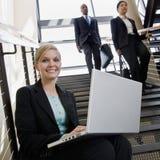 Empresaria que trabaja en la computadora portátil en las escaleras de la oficina Fotos de archivo libres de regalías