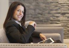 Empresaria que trabaja en la tableta en la oficina Imágenes de archivo libres de regalías