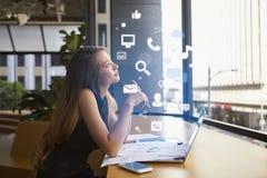 Empresaria que trabaja en una oficina que mira iconos del app foto de archivo libre de regalías