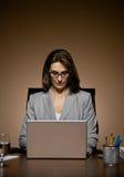 Empresaria que trabaja tarde y que pulsa en la computadora portátil Imágenes de archivo libres de regalías