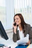 Empresaria que trabaja y que charla en su móvil Imagen de archivo
