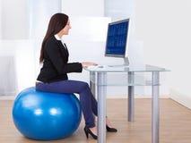 Empresaria que usa el ordenador mientras que se sienta en bola de los pilates Imagenes de archivo