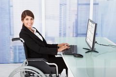 Empresaria que usa el ordenador mientras que se sienta en la silla de ruedas Fotografía de archivo libre de regalías