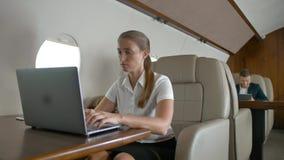 Empresaria que usa el ordenador portátil en el avión metrajes