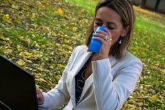 Empresaria que usa el ordenador portátil en descanso para tomar café en naturaleza imagen de archivo libre de regalías