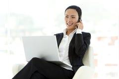 Empresaria que usa el ordenador portátil en rodillas Imagen de archivo libre de regalías