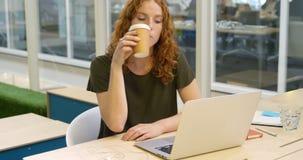 Empresaria que usa el ordenador portátil mientras que comiendo el café 4k almacen de metraje de vídeo