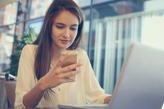 Empresaria que usa el ordenador portátil y mandando un SMS con el teléfono celular en oficina Foto de archivo