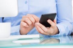 Empresaria que usa el teléfono móvil que se sienta delante del ordenador imagen de archivo
