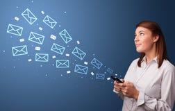 Empresaria que usa el tel?fono con concepto del correo alrededor imagen de archivo libre de regalías