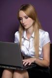 Empresaria que usa la computadora portátil en oficina Imagenes de archivo