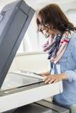 Empresaria que usa la fotocopiadora en oficina creativa Foto de archivo libre de regalías