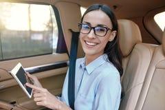 Empresaria que usa la tableta digital en el coche foto de archivo