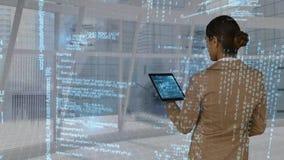 Empresaria que usa la tableta digital mientras que datos proyectados en el interfaz que se mueve detrás de ella
