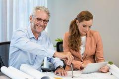 Empresaria que usa la tableta digital mientras que compañero de trabajo que trabaja en modelo con el compás Imagen de archivo