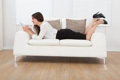 Empresaria que usa la tableta digital mientras que miente en el sofá Fotos de archivo libres de regalías