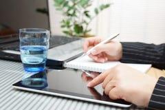 Empresaria que usa la tableta, el ordenador portátil y la escritura Imagen de archivo libre de regalías