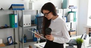 Empresaria que usa la tableta y bebiendo el café en oficina moderna almacen de video