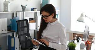 Empresaria que usa la tableta y sonriendo en oficina moderna almacen de metraje de vídeo