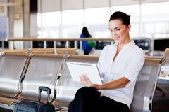 Empresaria que usa la tablilla en el aeropuerto Imágenes de archivo libres de regalías