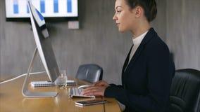 Empresaria que usa PC de sobremesa en el escritorio de oficina almacen de video