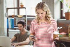Empresaria que usa smartphone mientras que sostiene el café en oficina Imágenes de archivo libres de regalías