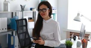 Empresaria que usa smartphone y sonriendo en cámara en oficina moderna almacen de metraje de vídeo