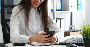 Empresaria que usa smartphone y sonriendo en oficina moderna almacen de metraje de vídeo