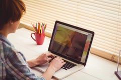 Empresaria que usa su ordenador portátil en el escritorio Foto de archivo libre de regalías