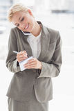 Empresaria que usa su smartphone y escribiendo notas Fotografía de archivo