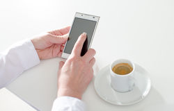 Empresaria que usa un smartphone durante descanso para tomar café Imagen de archivo