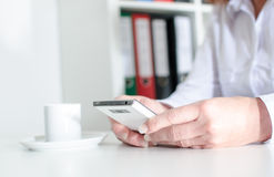Empresaria que usa un smartphone durante descanso para tomar café Imagen de archivo libre de regalías