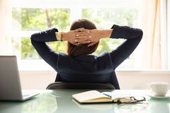 Empresaria relajada que se sienta en oficina imagen de archivo libre de regalías