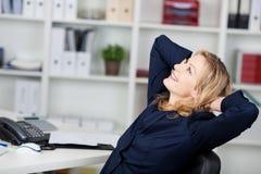 Empresaria Relaxing With Hands detrás de la cabeza en el escritorio Foto de archivo