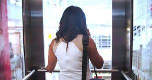 Empresaria Riding Elevator And que habla en el teléfono móvil almacen de metraje de vídeo
