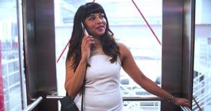 Empresaria Riding Elevator And que habla en el teléfono móvil almacen de video