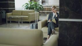 Empresaria rubia alegre que se sienta en butaca en el pasillo del hotel que habla en el teléfono móvil y que escribe en la sonris almacen de metraje de vídeo
